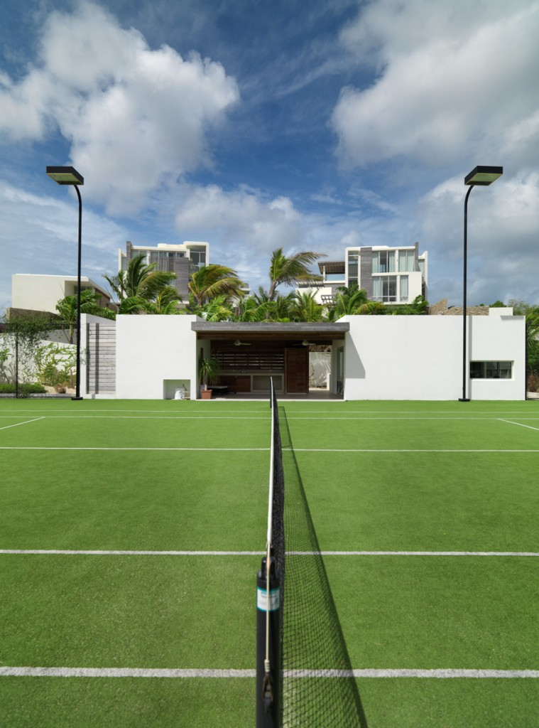 The illuminated tennis courts and gym with the villas above in the background
