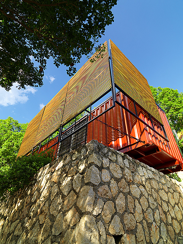 the container and suns-screens perched on top of the rubble stone retaining wall