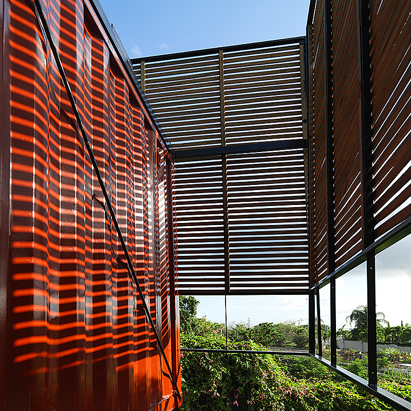 timber sunscreens create interesting shadows of crenelated surface of the container